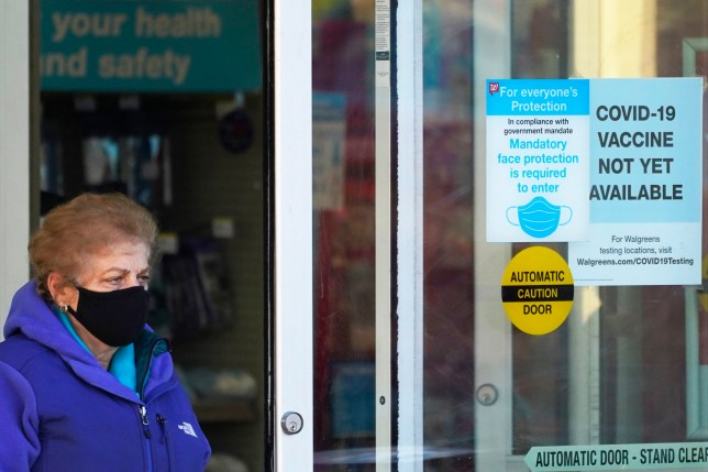 A customer wears a mask as she walks out of a Walgreen's pharmacy store and past a sign advising that a COVID-19 vaccine is not yet available at Walgreens in Northbrook, Ill., Thursday, Dec. 4, 2020. (AP Photo/Nam Y. Huh)