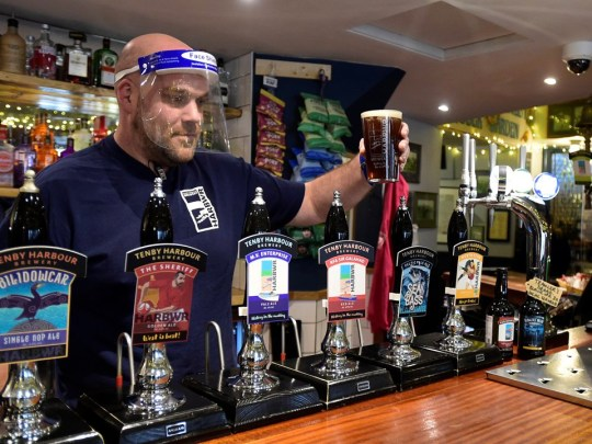 A barman wearing a visor serves pints at a pub