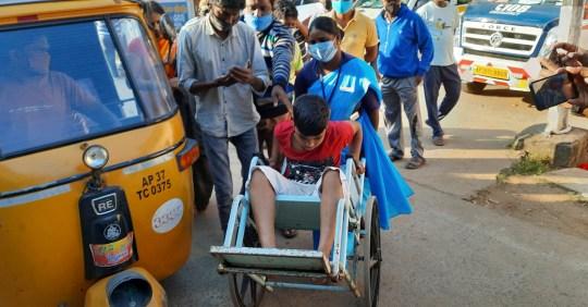 Un jeune patient est amené en fauteuil roulant à l'hôpital gouvernemental du district d'Eluru, dans l'État d'Andhra Pradesh, en Inde, le dimanche 6 décembre 2020. Plus de 200 personnes ont été hospitalisées en raison d'une maladie non identifiée dans cette ancienne ville célèbre pour son tissage à la main. des produits.  (Photo AP)