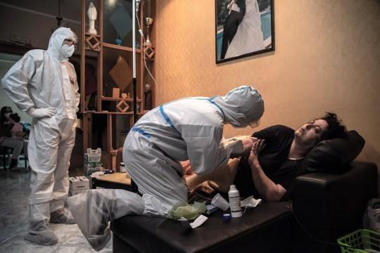 Un médecin et une infirmière lors de l'administration d'une thérapie à un patient covid-19 à son domicile le 27 novembre 2020 à Somma Vesuviana, Italie.