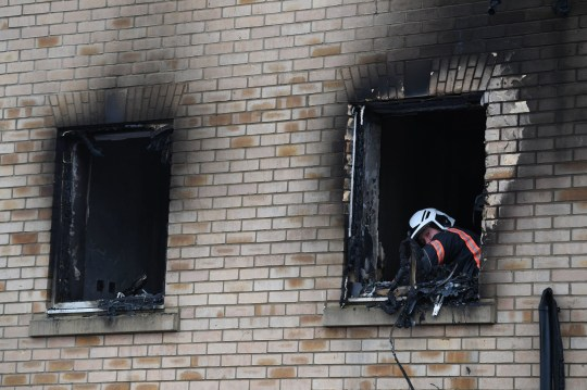A fire investigator in the burnt out window of a house fire on Buttercup Avenue, Eynesbury, Cambridgeshire, where a three-year-old boy and a seven-year-old girl died. A 35-year-old woman and a 46-year-old were also injured in the fire at the three-storey house, which police believe broke out around 7am Thursday morning. PA Photo. Picture date: Friday December 11, 2020. See PA story POLICE Eynesbury. Photo credit should read: Joe Giddens/PA Wire