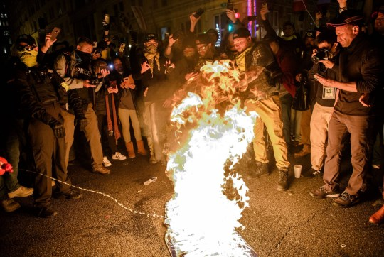 Mandatory Credit: Photo by Amy Harris/REX (11539859dt) A 'Proud Boy' adds fuel to a 'Black Lives Matter' flag on fire as leader Enrique Tarrio and other members gather in the streets following the 'Million MAGA March' on December 12, 2020 in Washington, DC. Demonstrators Participate In 'Million MAGA March' In DC Following Supreme Court Decision To Reject Texas Lawsuit Challenging Biden's Victory, Washington, USA - 12 Dec 2020