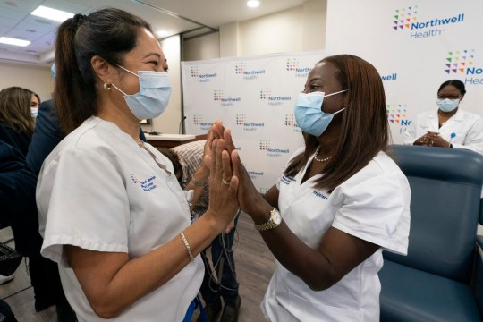 Nurse Annabelle Jimenez, left, congratulates nurse Sandra Lindsay after she is inoculated with the Pfizer-BioNTech COVID-19 vaccine, Monday, Dec. 14, 2020, at the Jewish Medical Center, in the Queens borough of New York. (AP Photo/Mark Lennihan, Pool)
