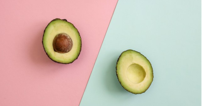 Flat lay of one halved fresh avocado over pink and blue background