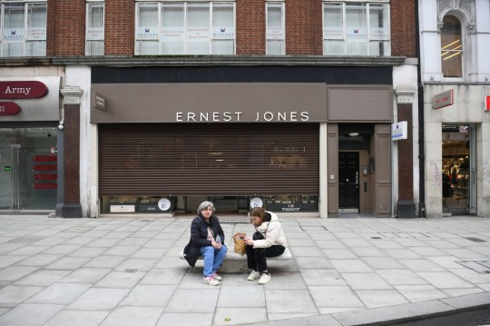 Two women sit on a bench in Oxford Street, central London,