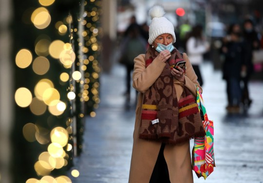 A member of the public wearing a face covering shopping on Buchanan Street in Glasgow,