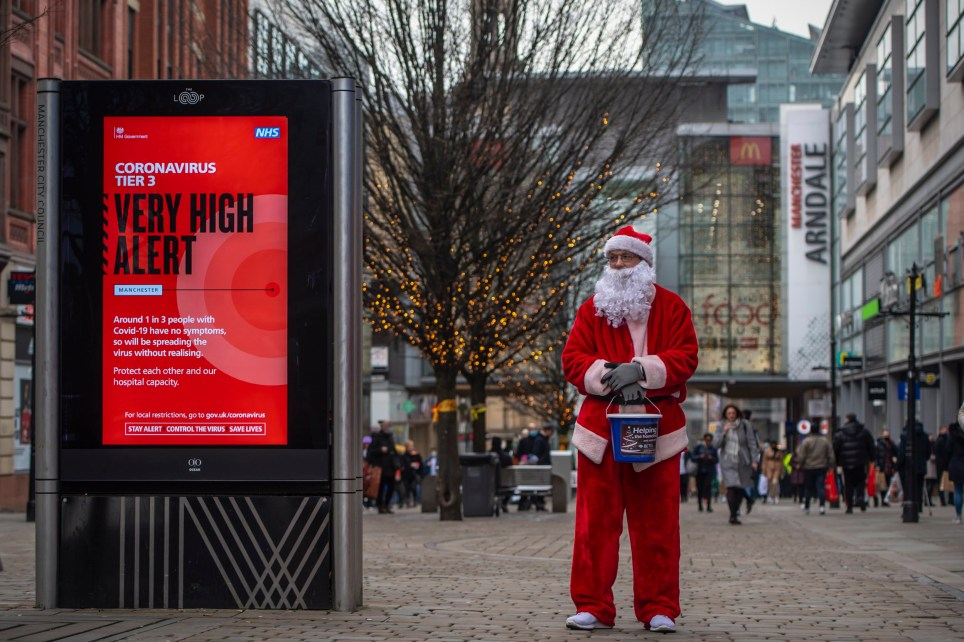 A charity worker from Help The Homeless dressed as Father Christmas collects donations on Market Street in Manchester city centre on December 22