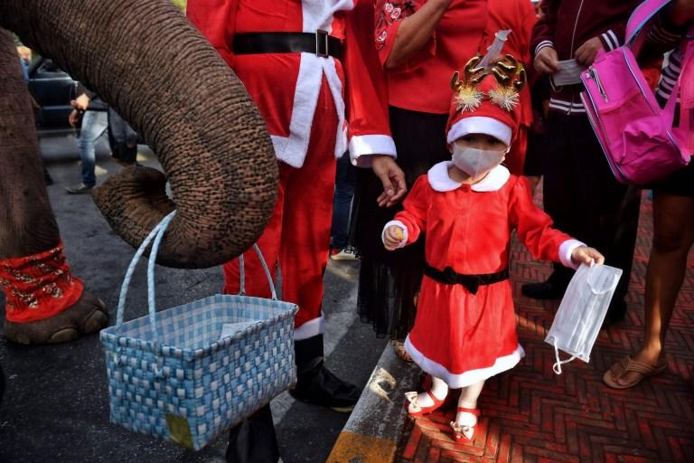 Un étudiant (R) prend un masque facial dans un panier tenu par un éléphant (L) du Palais des éléphants d'Ayutthaya dans un costume de Père Noël et portant un masque facial à l'extérieur de l'école Jirasat Wittaya dans la province centrale de la Thaïlande d'Ayutthaya le 23 décembre 2020.