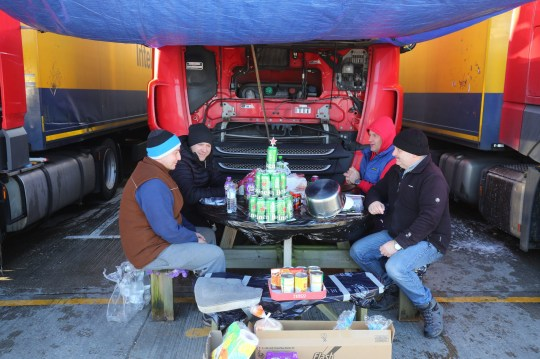 Polish lorry drivers, with a makeshift Christmas tree fashioned out of empty Heineken cans, share Christmas Day food and drinks at a truck stop near Folkestone, Kent. Hundreds of travellers are spending Christmas Day as they wait to resume their journey to the Port of Dover and across The Channel now that the borders with France have reopened. PA Photo. Picture date: Friday December 25, 2020. Delays continue as travellers must be able to show proof of a negative test result carried out within the past 72 hours in order to be able to cross into France. See PA story HEALTH Coronavirus. Photo credit should read: Gareth Fuller/PA Wire