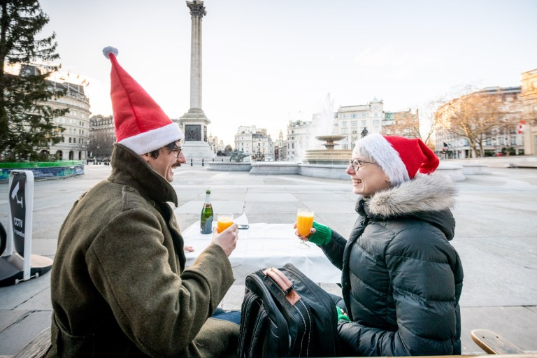 LONDON, ENGLAND - DECEMBER 25: A couple welcome in Christmas as they enjoy their morning together in an empty Trafalgar Square on December 25, 2020 in London, United Kingdom. Last week, the British government scrapped a plan to allow household mixing in England for five days over Christmas. In London and southeast, household mixing was banned, and in other parts of the country indoor meetups were confined to Christmas Day. (Photo by Joseph Okpako/Getty Images)