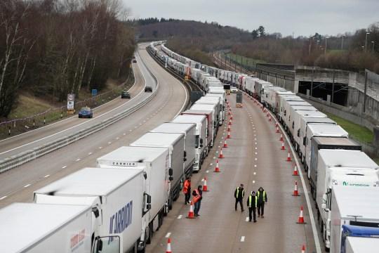 People walk amid lines of lorries queueing at the M20 motorway
