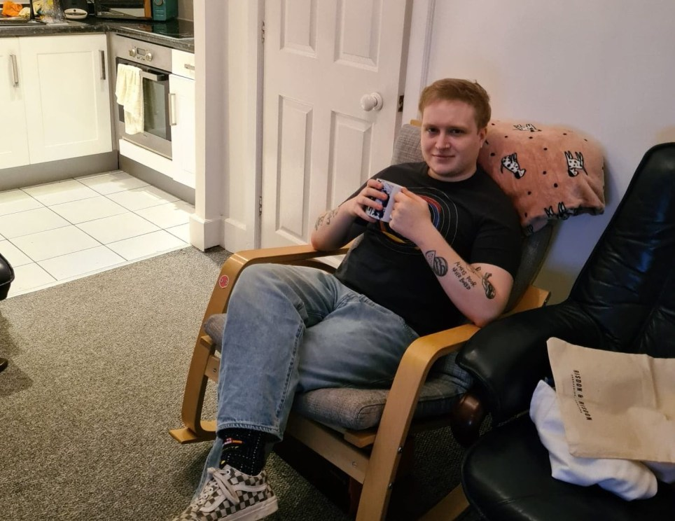 What I Rent: Adam, £450 a month for a two-bedroom flat in shrewsbury - Adam sitting in a chair drinking tea