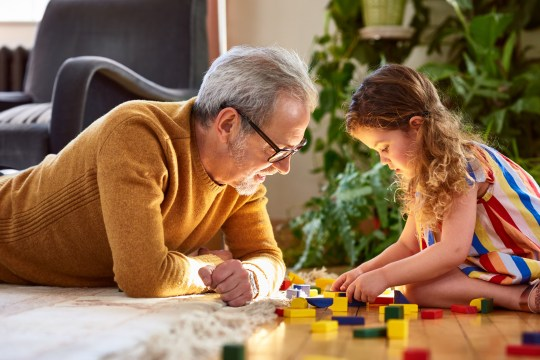 Man playing with lego bricks with a young girl