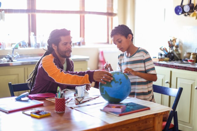 Father helping his son make a globe in his kitchen