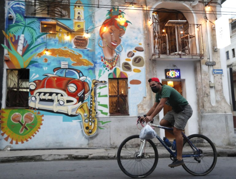 A man on a bicycle passes a graffiti, in Havana, Cuba, on January 11, 2021.
