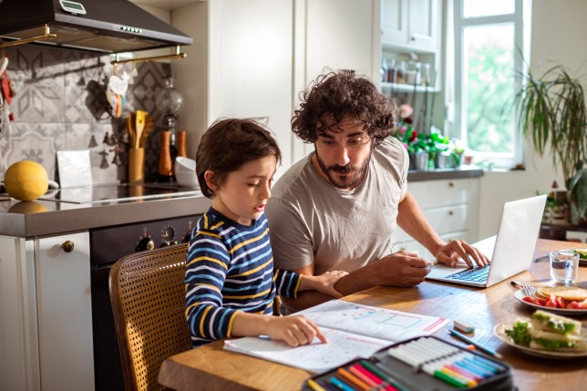 A father helps his son study on the laptop