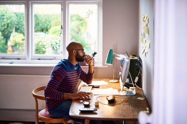 A man sitting at his desk working on a computer at home