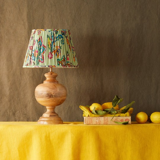 Brightly coloured lampshade on wooden base, on a lemon yellow tablecloth with lemons scattered on the table. Matthew Williamson's home.