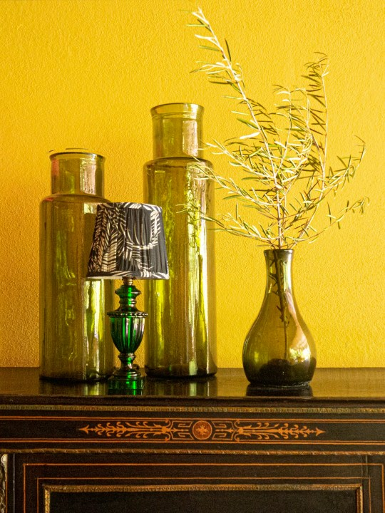 Glass vases and small green lamp against bright yellow wall. Matthew Williamson.