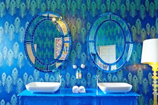 Bright blue bathroom with double sink and two large mirrors reflecting peacock print wallpaper