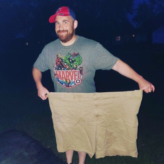 Man holding large pair of shorts after weight loss