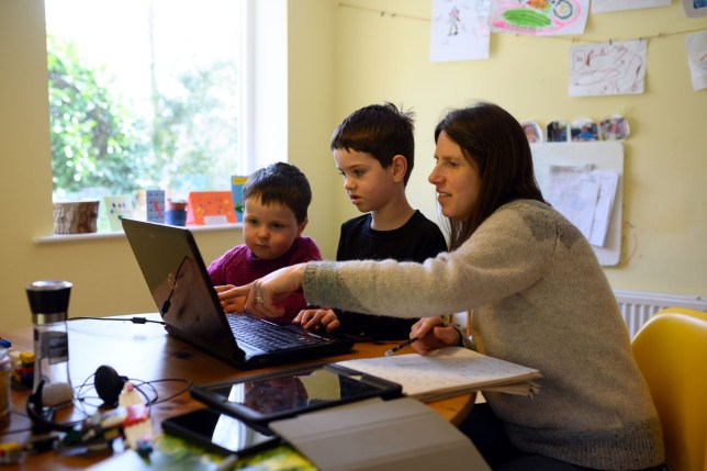 Leo (C), aged 6, and Espen, aged 3, are assisted by their mother Moira as they navigate online learning resources provided by their infant school in the village of Marsden, near Huddersfield, northern England on March 23, 2020.