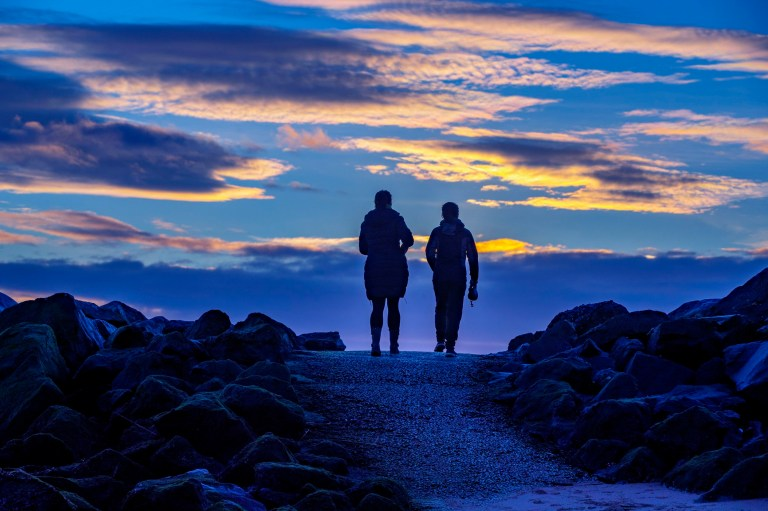 Two women walk their dogs at sunrise on New Brighton beach, Wirral. PA Photo. Picture date: Monday January 4, 2021. See PA story WEATHER Winter. Photo credit should read: Peter Byrne/PA Wire
