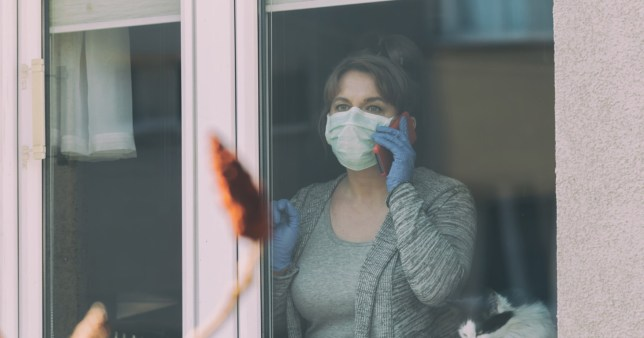 Shielding returns Woman using smartphone wearing a protective face mask and looking out the window of her home because of an epidemic of corona virus covid-19. Home quarantine and self isolation concept