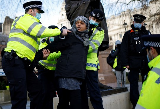 Police officers detain a protestor during an anti-COVID-19 lockdown demonstration outside the Houses of Parliament in Westminster, central London on January 6, 2021. - Britain toughened its coronavirus restrictions on Tuesday, with England and Scotland going into lockdown and shutting schools, as surging cases have added to fears of a new virus variant. (Photo by Tolga Akmen / AFP) (Photo by TOLGA AKMEN/AFP via Getty Images)
