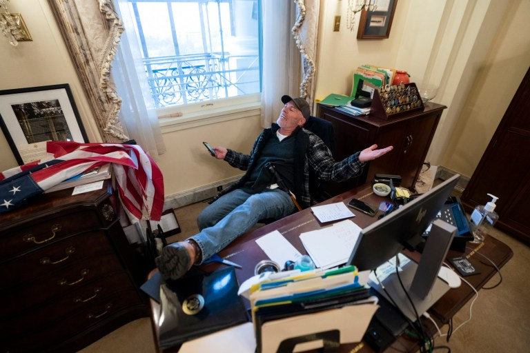 A supporter of US President Donald J. Trump sits on the desk of US House Speaker Nancy Pelosi, after supporters of US President Donald J. Trump breached the US Capitol security in Washington, DC, USA, 06 January 2021. Protesters stormed the US Capitol where the Electoral College vote certification for President-elect Joe Biden took place.