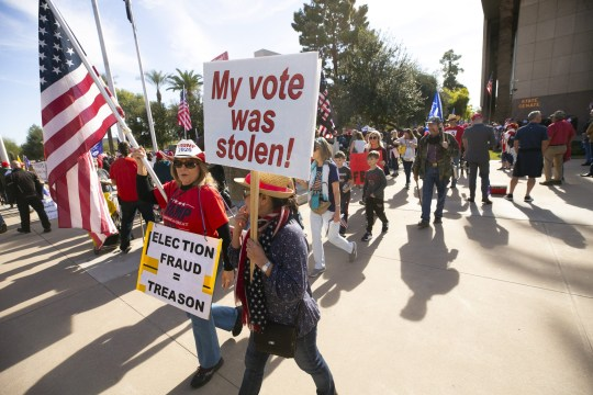 People participate in a pro-Trump rally at the state capitol in Phoenix. Trump called the investigations chief for Georgia's secretary of state and told him to 'find the fraud'.