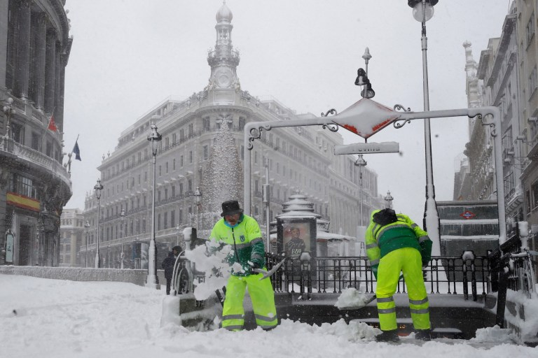 epa08927989 Workers plow snow for people to walk through at Gran Via Avenue in Madrid, Spain, 09 January 2021. Storm Filomena brought the heaviest snowfall in decades. EPA/BALLESTEROS