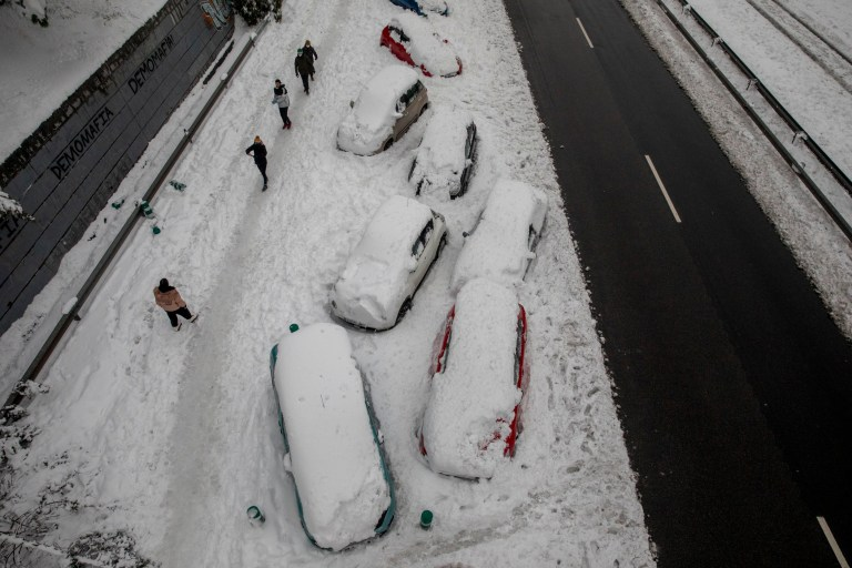MADRID, SPAIN - JANUARY 09: Cars are blocked on the snow as people walk past along the M-30 road during heavy snowfall on January 09, 2021 in Madrid, Spain. Spain is on red alert for a second day due to storm Filomena, which has brought unusually cold weather and heavy snowfalls. The storm has caused cancelled services and transport disruption. (Photo by Pablo Blazquez Dominguez/Getty Images)