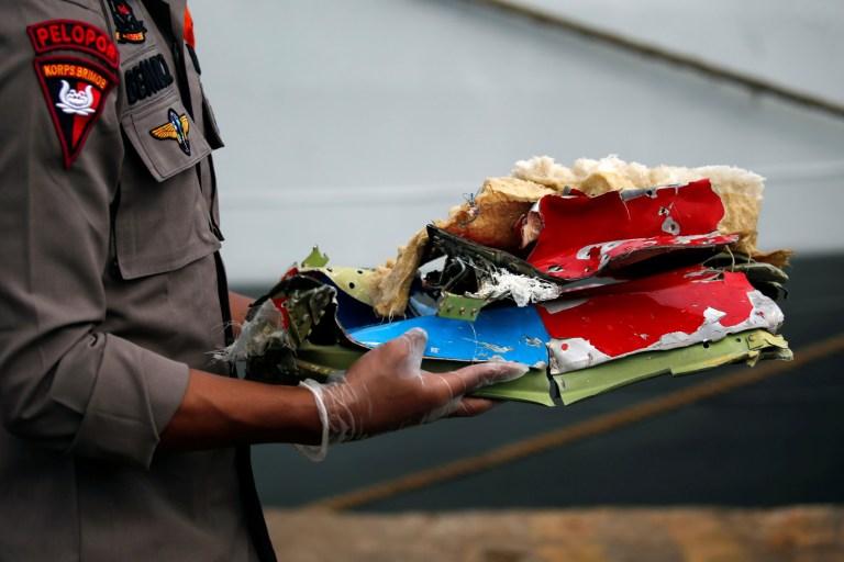 Un policier indonésien transporte des débris du vol SJ 182 de Sriwijaya Air, qui s'est écrasé en mer, au port de Tanjung Priok à Jakarta, Indonésie, le 10 janvier 2021. REUTERS / Willy Kurniawan