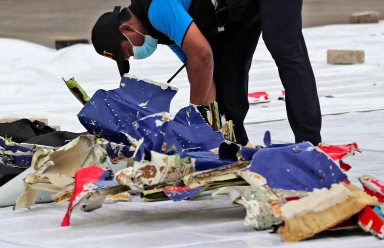 Un enquêteur du Comité national indonésien de la sécurité des transports inspecte des parties du vol 182 de Sriwijaya Air qui s'est écrasé dans les eaux au large de l'île de Java, au port de Tanjung Priok à Jakarta, en Indonésie, dimanche 10 janvier 2021. Des sauveteurs indonésiens ont retiré des parties du corps, des morceaux de des vêtements et des bouts de métal de la mer de Java tôt dimanche matin, un jour après que le Boeing 737-500 avec des dizaines de personnes à bord se soit écrasé peu de temps après le décollage de Jakarta, ont indiqué des responsables.  (Photo AP / Tatan Syuflana)