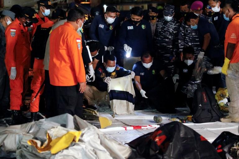 Des agents indonésiens d'identification des victimes de catastrophes (DVI) observent un tissu découvert en mer, soupçonné d'appartenir à l'un des passagers du vol SJ 182 de Sriwijaya Air, qui s'est écrasé en mer, au port de Tanjung Priok à Jakarta, en Indonésie, le 10 janvier 2021. REUTERS / Willy Kurniawan