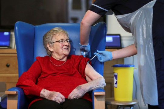 Resident Annie Innes, 90, receives a dose of the Pfizer-BioNTech COVID-19 vaccine at the Abercorn House Care Home in Hamilton, western Scotland, on December 14, 2020. - Britain has received some 800,000 doses of the vaccine in the first batch of an order of 40 million. Up to four million doses are expected by the end of December. The vaccine is administered in two doses, 21 days apart. The over-80s and health and social care staff are first in line to get the jab in the national rollout. (Photo by RUSSELL CHEYNE / POOL / AFP) (Photo by RUSSELL CHEYNE/POOL/AFP via Getty Images)