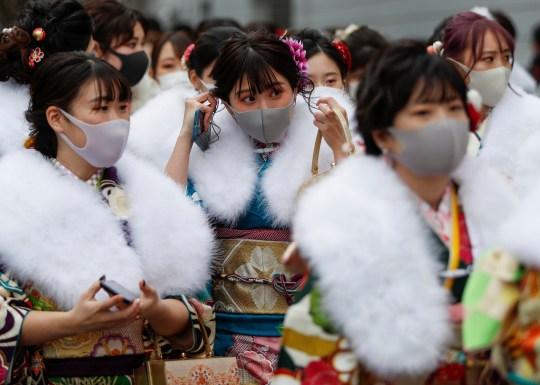Des jeunes vêtus de kimono portant des masques protecteurs quittent leur cérémonie de célébration de la Journée de la venue de l'âge.  Le Japon a découvert une nouvelle variante du coronavirus qui a été découverte chez des passagers arrivés à Tokyo en provenance du Brésil.