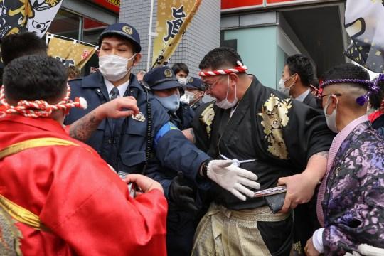Des policiers affrontent des hommes en kimonos près de Yokohama Arena.  Le Japon a découvert une nouvelle variante du coronavirus qui a été découverte chez des passagers arrivés à Tokyo en provenance du Brésil.