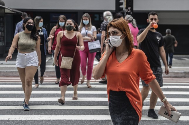 Pedestrians wearing face masks cross a street in Sao Paulo, Brazil,