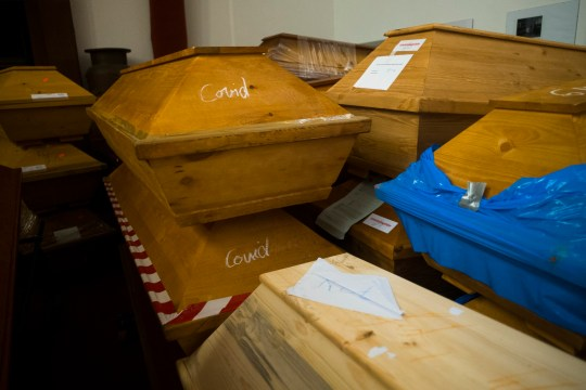 Caskets labelled with the word 'Covid' are stacked with others coffins in the memorial hall of the crematorium in Meissen, Germany, Monday, Jan. 11, 2021.