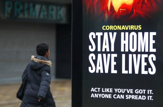 A person walks past a 'Stay Home Save Lives' government sign on Commercial road in Portsmouth during England's third national lockdown to curb the spread of coronavirus. PA Photo. Picture date: Tuesday January 12, 2021. Under increased measures people can no longer leave their home without a reasonable excuse and schools must shut for most pupils. See PA story HEALTH Coronavirus. Photo credit should read: Andrew Matthews/PA Wire