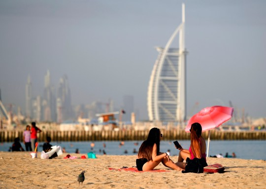 Woman sunbathers sit along a beach in the Gulf emirate of Dubai on July 24, 2020, while behind is seen the Burj al-Arab hotel. - After a painful four-month tourism shutdown that ended earlier in the month, Dubai is billing itself as a safe destination with the resources to ward off coronavirus. The emirate, which had 16.7 million visitors last year, had opened its doors to tourists despite global travel restrictions and the onset of the scorching Gulf summer in the hopes the sector will reboot before high season begins in the last quarter of 2020. (Photo by Karim SAHIB / AFP) (Photo by KARIM SAHIB/AFP via Getty Images)