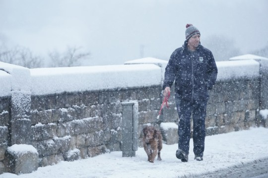 A dog walker makes his way through snow in Hexham, Northumberland. Heavy snow and freezing rain is set to batter the UK this week, with warnings issued over potential power cuts and travel delays. PA Photo. Picture date: Thursday January 14, 2021. Photo credit should read: Owen Humphreys/PA Wire