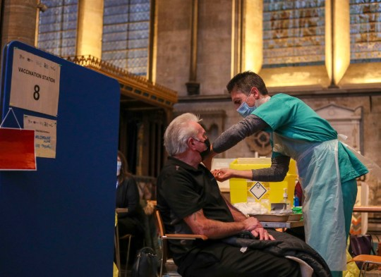Lynn Court receives an injection of the Pfizer coronavirus vaccine from Dr Ben Kay at Salisbury Cathedral, Wiltshire. Over-70s and extremely vulnerable people will start getting their vaccines this week.