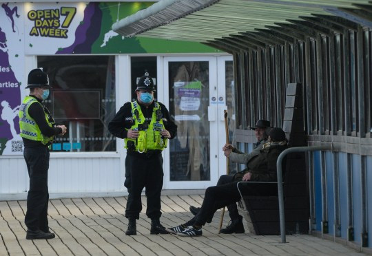 Police talking to two people sitting on a bench. Brits have ignored Boris Johnson's pleas to stay at home this weekend.