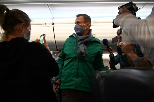 Passengers and journalists photographing Alexei Navalny being taken away. Russian authorities arrested Kremlin critic Alexei Navalny as he landed in Moscow.