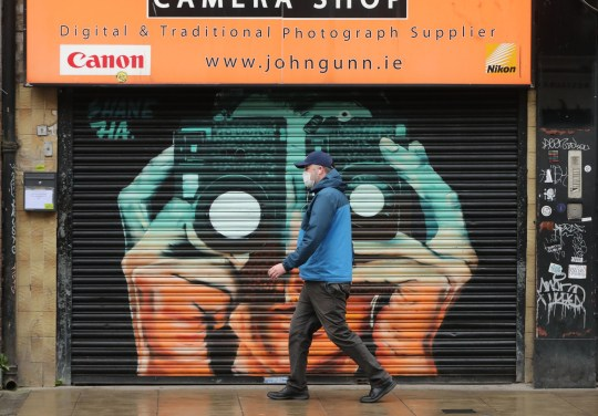 A man walks past a boarded up camera shop on Camden Street in Dublin city centre as Ireland remains in lockdown to help prevent the spread of coronavirus. Ireland's health service is potentially facing the most challenging week in its history with the number of Covid-19 patients requiring intensive care treatment having risen sharply since the end of December. Picture date: Monday January 18, 2021. PA Photo. See PA story IRISH Coronavirus. Photo credit should read: Niall Carson/PA Wire