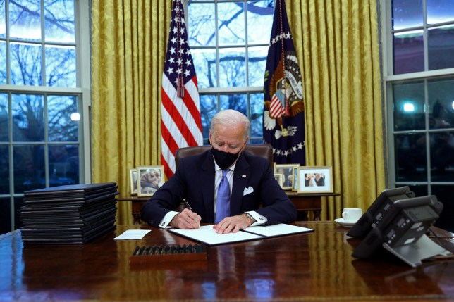 President Joe Biden signs executive orders in the Oval Office of the White House