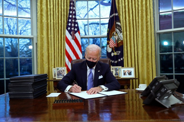 U.S. President Joe Biden signs executive orders in the Oval Office of the White House in Washington, after his inauguration as the 46th President of the United States, U.S., January 20, 2021. REUTERS/Tom Brenner TPX IMAGES OF THE DAY